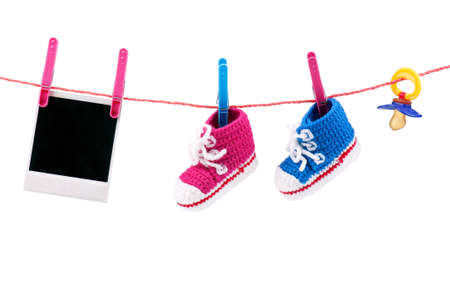 Baby bootees, photo and dummy on the clothesline on a white background photo