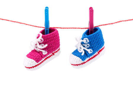 Baby bootees on the clothesline on a white background photo