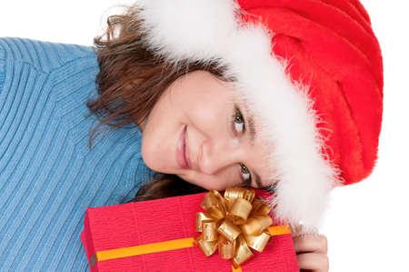 Christmas girl holding gift wearing Santa hat over white background photo