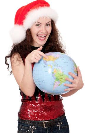 Smiling christmas girl holding globe wearing Santa hat. Isolated on white background. photo