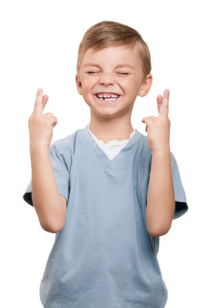 fingers crossed: Portrait of superstitious little boywith crossed fingers over white background Stock Photo