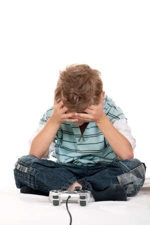 Little child playing a video game on white background photo