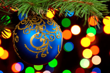 Blue bauble on green christmas firtree on abstract blue background Stock Photo - 11454950