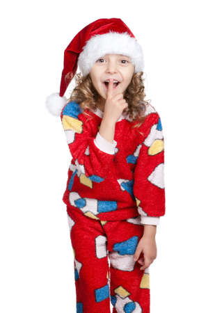 Portrait of Little girl in pajamas and santa hat with silence gesture over white background photo