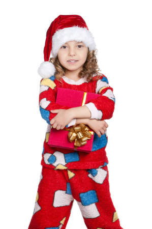 Portrait of happy Little girl in pajamas and santa hat with gift box over white background Stock Photo - 11464745