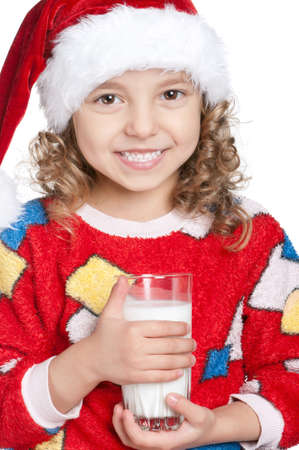 Portrait of happy little girl in pajamas and santa hat with glass of milk over white background Stock Photo - 11467496