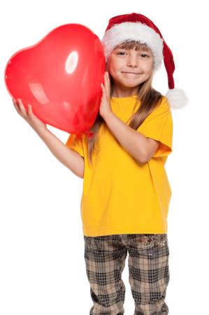 Portrait of little girl in santa hat with red heart balloon over white background Stock Photo - 11479013