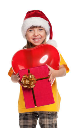 Portrait of little girl in santa hat with red heart balloon over white background photo