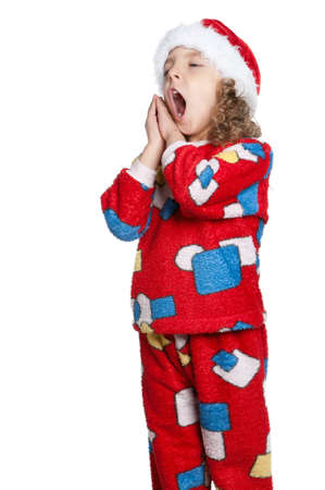 tiredness: Portrait of Little girl in pajamas and santa hat over white background Stock Photo