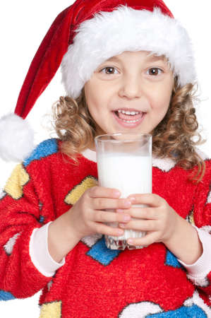 Portrait of happy little girl in pajamas and santa hat with glass of milk over white background photo