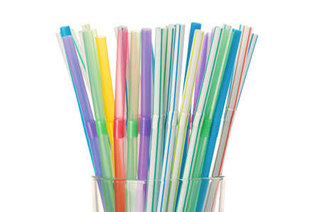 Colorful cocktail straws in glass on a white background photo