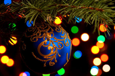 Blue bauble on green christmas firtree on abstract blue background photo