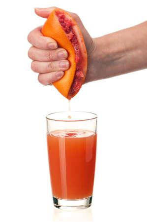 squeezed: Vaso de jugo de pomelo fresco y de la mano con la mitad de la toronja en el fondo blanco Foto de archivo