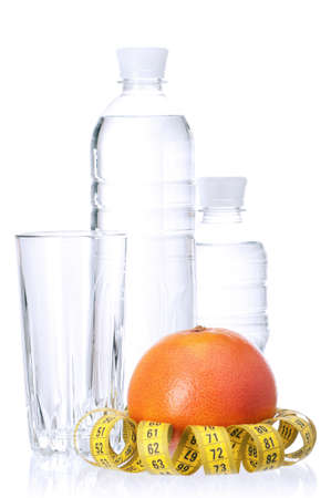 Fresh ripe grapefruit with measure tape and Bottled water on white background photo