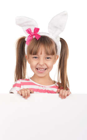 Easter concept image. Portrait of happy little girl with bunny ears and empty white board over white background. Stock Photo - 11866277