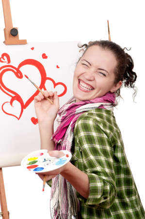Love or Valentine day - concept image. Beautiful girl with brushes near easel, painting on canvas.. photo