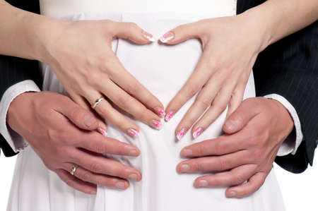 nuptial: Hands of happy bride and groom with heart Stock Photo