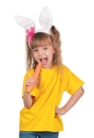 Easter concept image. Portrait of happy little girl with bunny ears and carrot over white background. photo