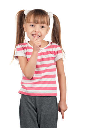 Portrait of little girl with silence gesture over white background photo