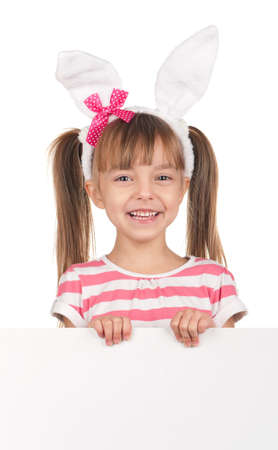 Easter concept image. Portrait of happy little girl with bunny ears and empty white board over white background. photo