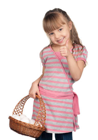 Happy little girl holding basket of eggs and giving you thumb up over white background photo