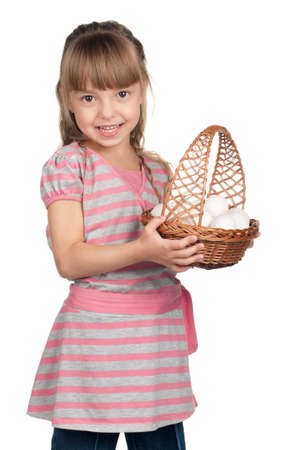 Happy little girl holding basket of eggs over white background photo