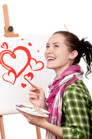 Love or Valentine day - concept image. Beautiful girl with brushes near easel, painting on canvas.. Stock Photo - 12014444