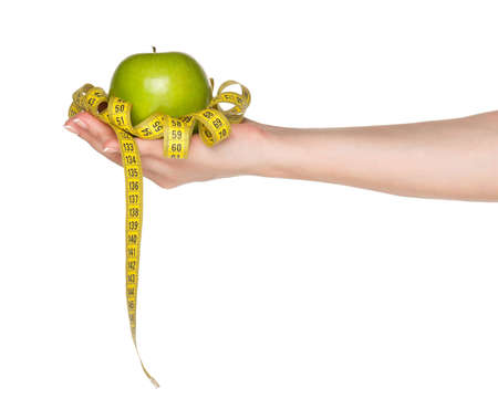 Woman hand with green apple and measure tape isolated on white background photo