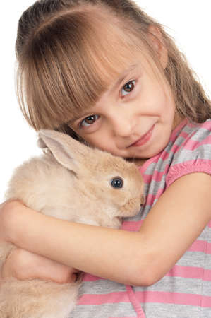 Easter concept image. Portrait of happy little girl with adorable rabbit over white background. photo