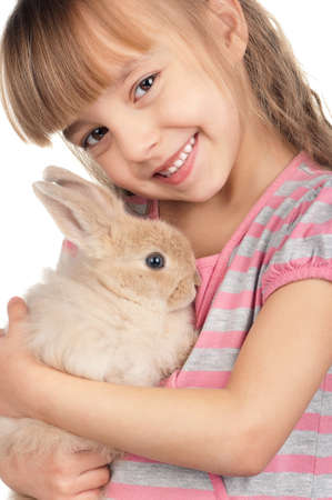 Easter concept image. Portrait of happy little girl with adorable rabbit over white background. Stock Photo