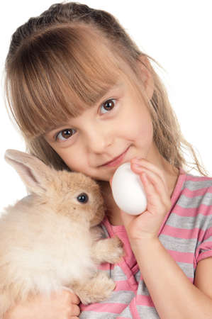 Easter concept image. Portrait of happy little girl with adorable rabbit and egg over white background. photo