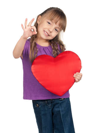 Portrait of little girl holding red heart and gesturing OK over white background photo