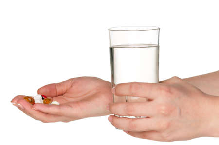 Woman hands with pills and glass of water isolated on white background photo