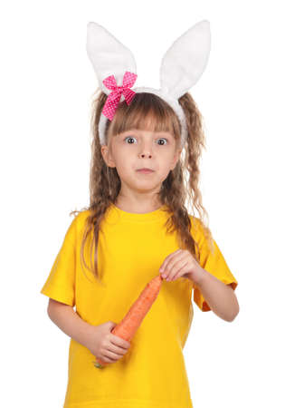 Portrait of surprised little girl with bunny ears with carrot over white background photo