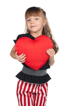 Portrait of little girl holding red heart over white background