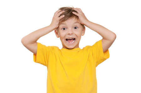 Portrait of shocked little boy with hands on head over white background photo