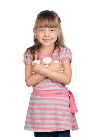 Happy little girl holding eggs over white background photo