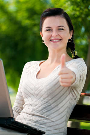Modern young business woman with notebook computer in park outdoors photo