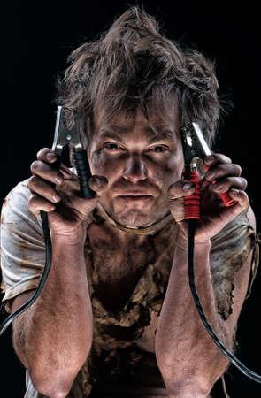 broken car: Portrait of funny electrician over black background