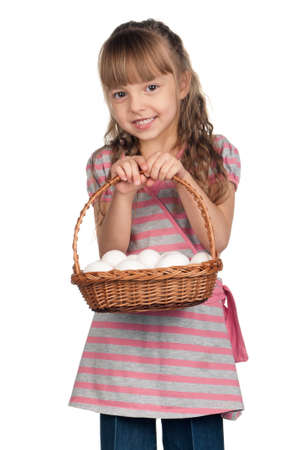 Happy little girl holding basket of eggs over white background photo
