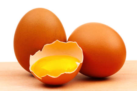yolk: Fresh chicken eggs on wooden board over white background