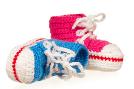 new born baby girl: Handmade blue and pink baby booties isolated on white background