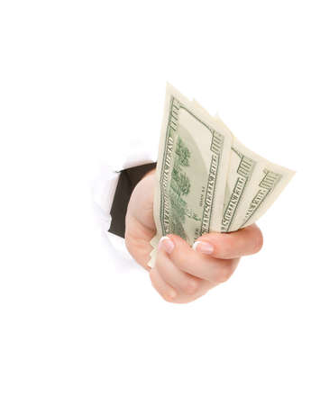 Woman hand with dollars through a hole in paper isolated on white background photo