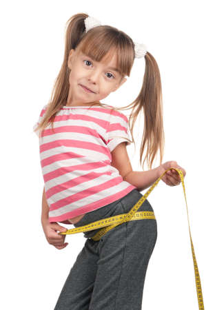 Portrait of little girl with yellow measure over white background photo