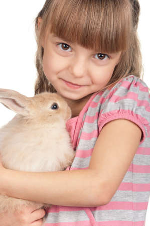 Easter concept image  Portrait of happy little girl with adorable rabbit over white background  photo