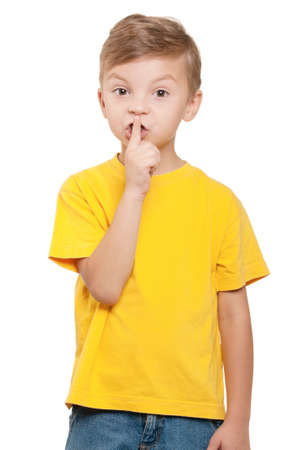 noiseless: Portrait of beautiful little boy with silence gesture over white background