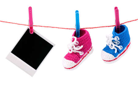 Baby bootees and photo hanging on the clothesline on a white background photo