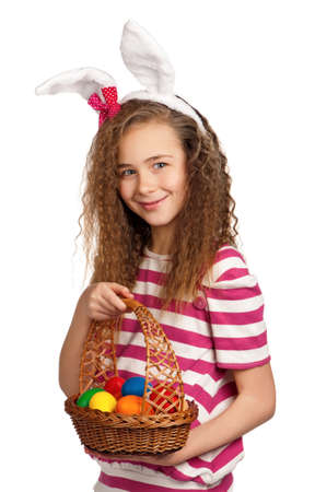 Happy girl with bunny ears, holding basket of eggs isolated on white background photo