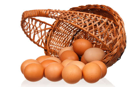Brown eggs in the wicker basket over white background photo