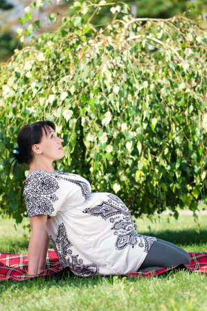 Happy pregnant woman in the park outdoors photo